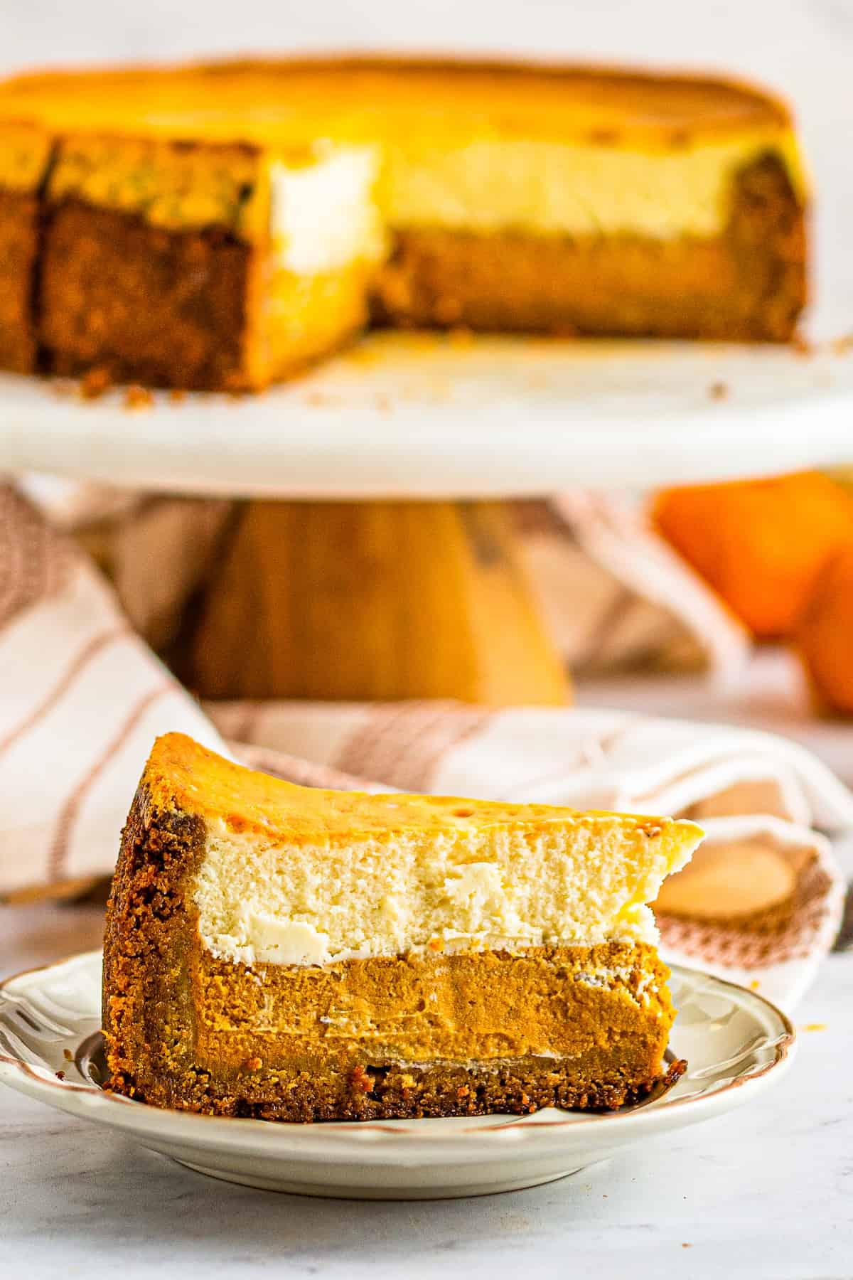 slice of layered pumpkin pie cheesecake on white plate