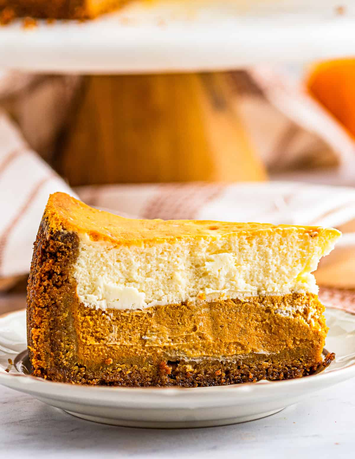 up close slice of layered pumpkin pie cheesecake on white plate